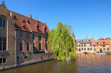 Bruges, Belgium-May 03, 2018:  Tourists are waiting for free tourist boat. Beautiful canal and old, traditional houses in the town of Bruges (dutch: Brugge)