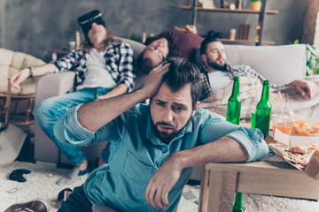 What we did last night? Bearded, upset, unhappy guy suffering from headache after night events, woke up on the floor holding hand on head, his drunk friends sleeping on couch on blurred background