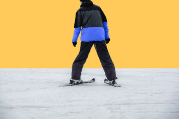 Skiing man on ski in jacket ready for skiing isolated on yellow