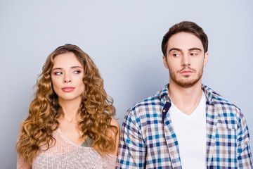 Conflict insult disagreement distrust fight cheat quarrel crisis concept. Portrait of modern couple in casual outfits looking at each other with eyes isolated on grey background