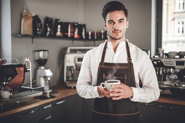 Professional barista in apron holding cup of coffee at cafe