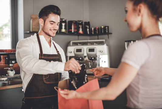 Professional barista giving shopping bag to customer at coffee shop, cafe small business