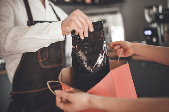 Professional barista giving coffee pack into shopping bag for customer at cafe