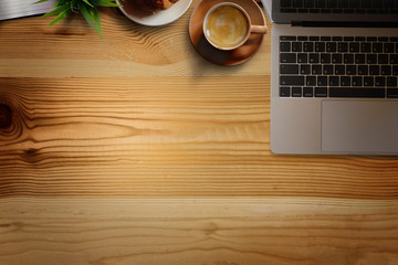 Office wooden desk with laptop, coffee cup and plant. Business workspace and copy space.