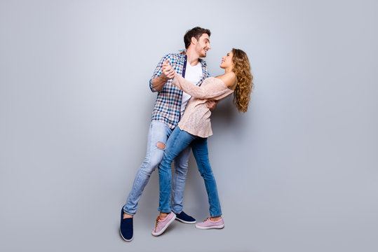 Full body portrait of creative cheerful couple in casual outfits dancing enjoying activity isolated on grey background. Move motion life art concept