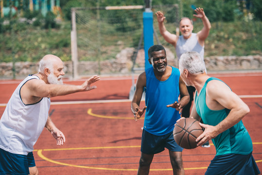 interracial elderly sportsmen playing basketball together on playground