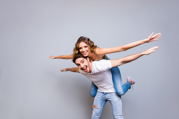 Low angle view portrait of cheerful funky couple, fancy man carrying on back charming woman holding hands to side making air plane isolated on grey background