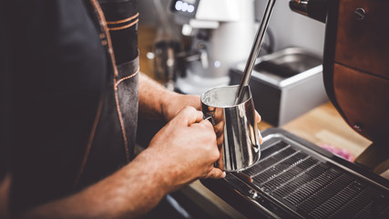 Barista steaming milk using coffee machine, close up view on hands during preparation