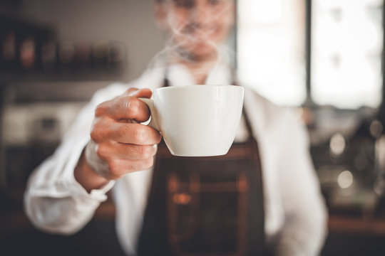 Barista presents cup of hot coffee at cafe, coffee shop business