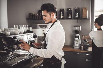 Barista preparing coffee using machine in the cafe