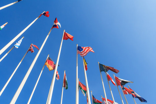 Bottom view of a rows of flags of different countries of the world, flutters in the wind, against a clear blue sky with copy space