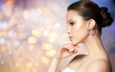 beauty, jewelry, people and luxury concept - close up of beautiful asian woman face with earring over holidays lights background
