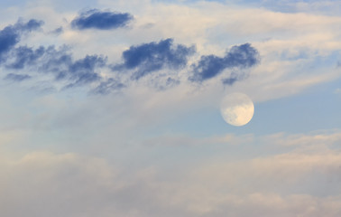 Moon surrounded by clouds at sunset