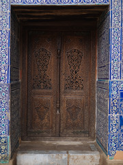 Ornamental carved door in tiled oriental wall