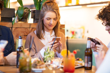 leisure, people and technology concept - happy friends with smartphones eating and drinking at restaurant