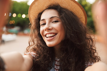 Young brunette woman 18-20 with curly brown hair, smiling and taking selfie photo while walking in hipster place or modern park with colorful illumination background