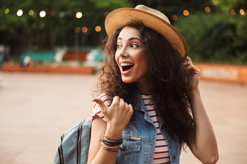 Photo of excited pretty woman 18-20 with curly brown hair, laughing and pointing finger aside while walking in hipster spot or modern park with colorful lamps background