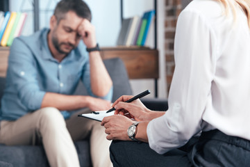 cropped image of female counselor writing in clipboard while depressed male patient sitting on sofa at office