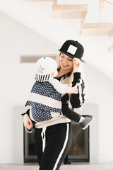 Stylish young mom keeps in ergo backpack of her cute year-old baby at home in a beautiful interior Convenience for mom.