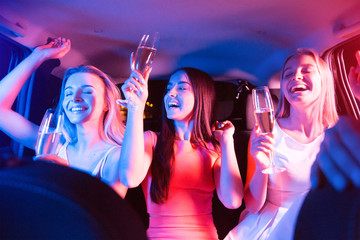 Beautiful girls are parting in car. They are having a lot of fun. They are moving with their hands, laughing and keeping eyes closed. Blonde girl and brunette girl are holding glasses of champagne.