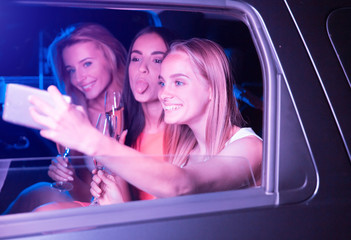 Funny picture of girls sitting in car and taking selfie. Blonde girl is holding phone in hand. Brunette is showing up her tongue. Another blonde girl is looking on camera and posing.
