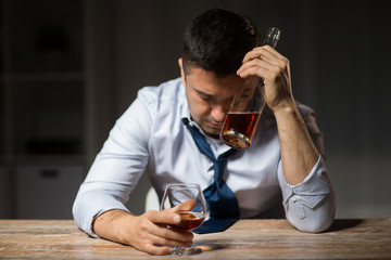 alcoholism, alcohol addiction and people concept - male alcoholic with bottle drinking brandy at table at night