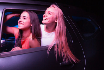Two happy girls are looking outside of car. They are looking straight forward and smiling. Blonde hair is waving. It is night outside.