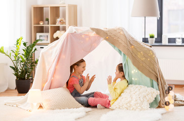 childhood, hygge and friendship concept - little girls playing clapping game in kids tent or teepee at home