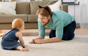 family, fatherhood and people concept - happy red haired father wearing cat ears headband playing with little baby daughter at home
