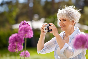 photography, leisure and people concept - happy senior woman with camera photographing flowers blooming at summer garden