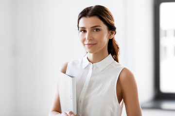 business, people and corporate concept - businesswoman or realtor with folder at office