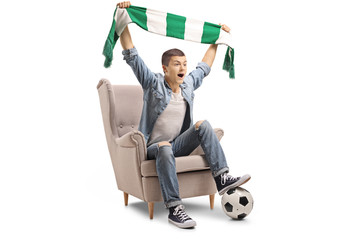 Overjoyed teenage soccer fan with a scarf and a football sitting in an armchair