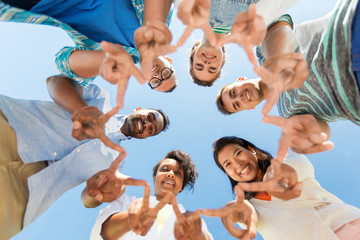 people, friendship and international concept - group of happy smiling friends outdoors standing in circle and showing peace hand sign