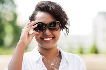 people, summer and eyewear - happy african american young woman in sunglasses outdoors