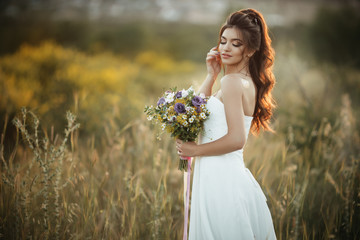 Beautiful young bride is holding fashion bouquet of wildflowers in yellow field, nature wedding concept