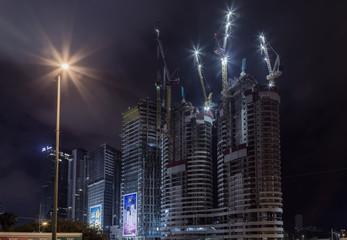 Night Tel Aviv. Night Tel Aviv. Tower cranes towering above multi-storey buildings.