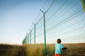 little child refugee near high and long fence with barbed razor wire outdoors