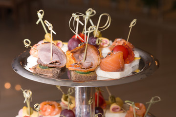 Snack for buffet on wooden skewers on a metal tray and a dark background