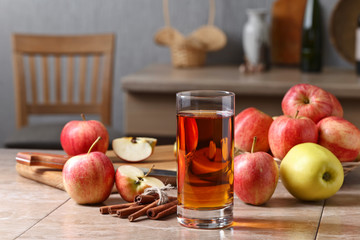Glass of apple juice , apples and cinnamon sticks .