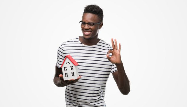 Young african american man holding house doing ok sign with fingers, excellent symbol