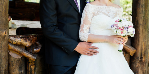 Beautiful bride and groom hugging at wedding day outdoors. Wedding couple in love at wedding day