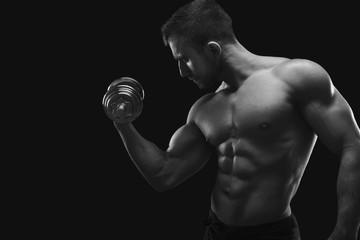 Strong man with dumbbell showing muscular body