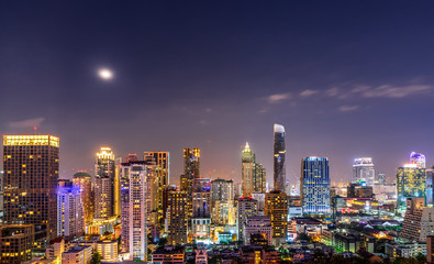 urban night cityscape with full moon and beautiful sky