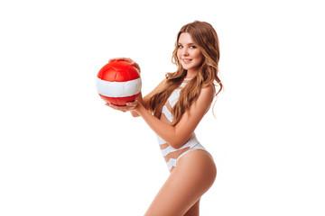 Pretty bikini model holding red ball in studio