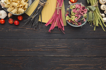 Dry mixed pasta on wooden background, top view
