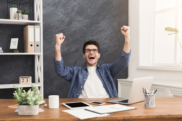 Young happy businessman in office with computer