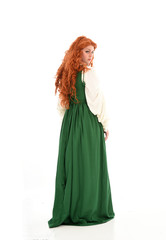 full length portrait of red haired girl wearing long green gown,. standing pose with back to the camera, isolated on white studio background.