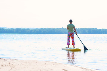 Woman sails on a SUP board in large river