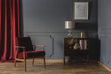 Real photo of a corner of a retro living room interior with elegant, beige lamp on a wooden cabinet next to a red armchair