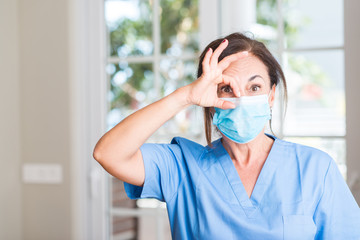 Middle aged doctor woman with happy face smiling doing ok sign with hand on eye looking through fingers